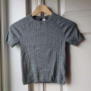 Fin militärgrön/grå tröja som är lite ribbad!😍 Skicket är jättebra trots att den är använd! Storleken är XS men passar även S om man vill ha en tight fit. Lite liten på mig som oftast har M i tighta tröjor. Köparen står för frakten!