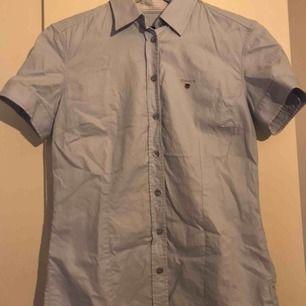 En ljusblå äkta gantskjorta i storlek 36. Figursydd och kortärmad.