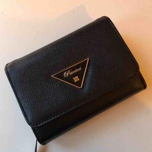 """En svart liten plånbok med mycket fack. Gulddetaljer. Köpt på butiken """"väskan""""."""