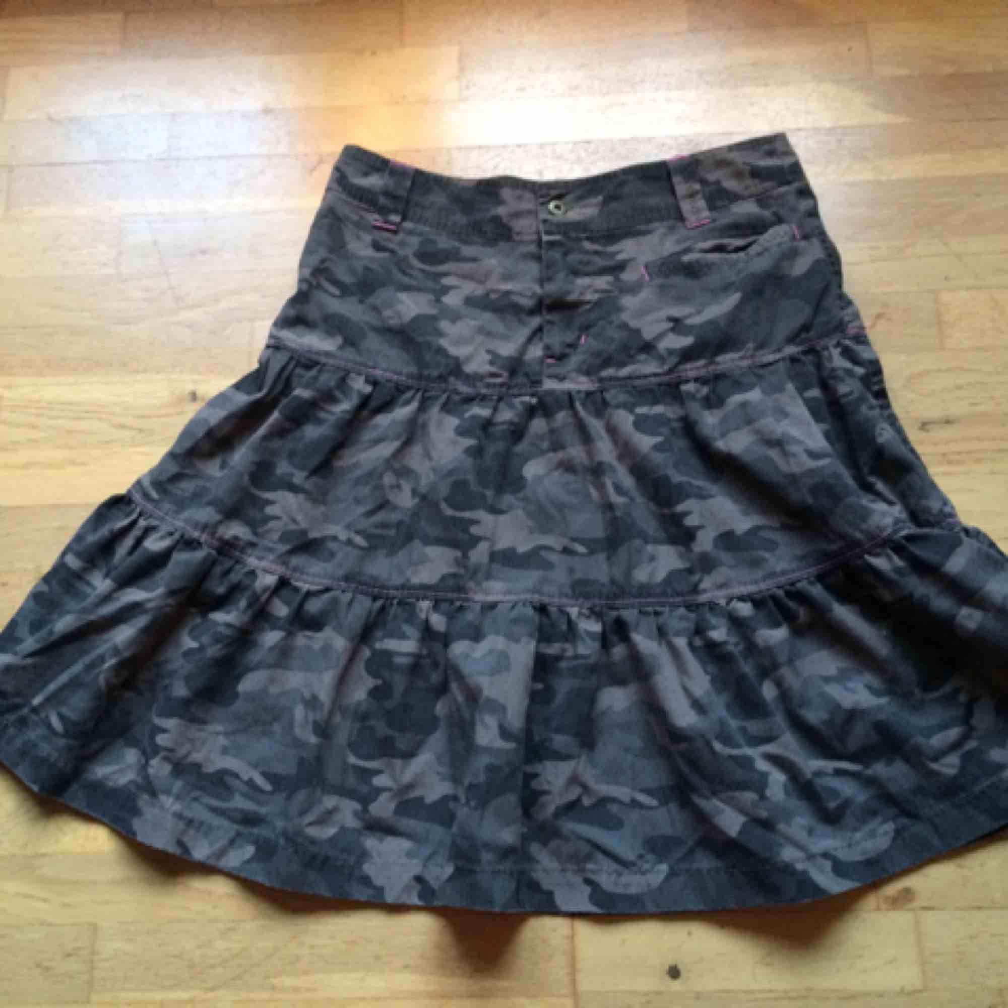 Kamouflagemönstrad kjol med rosa detaljer. En ficka fram och 2 baktill. Storlek M. Använd men i fint skick. Frakt: 59 kr i postens påse 🌸. Kjolar.