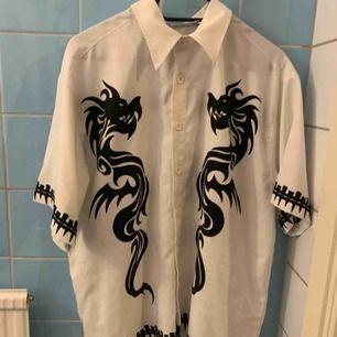 Vit skjorta med svarta drakar på. Använd typ 2 gånger!