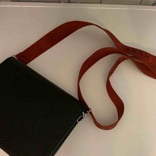 Svart väska med vinrött band. Aldrig använd!