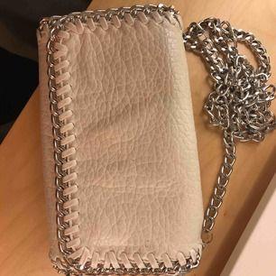 """Super sött vit väska från tiamo!! Inköpt för 450 säljes för 100kr då det finns ett litet hål inuti väskan av tyget men inte """"väskan """" , inget åker ut hel enkelt ! Så där av det låga priset :) ljuset gör tyvärr att den ser lite missfärgad"""