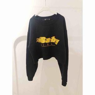 Svart croppad sweatshirt med tryck och texten Baby Girl från Missguided. Använd en gång. Storlek S.