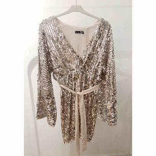 Glittrig klänning med bälte och vida ärmar. Storlek 38 (liten, passar 36), från Boohoo. Använd en gång.
