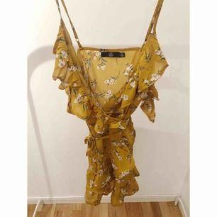 Gul blommig omlottklänning med volanger. Storlek 36, från Missguided.