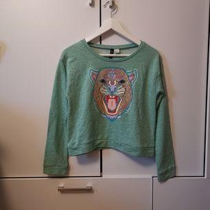 Grön tröja med tryck i storlek 36. Frakten ligger på 44 kr.