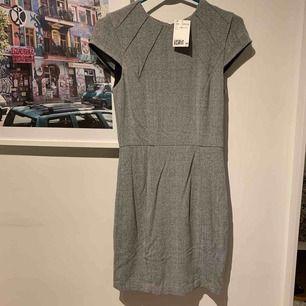 Så fin klänning som är helt oanvänd med lappen kvar, sitter super fint och är figur nära. Klänningen har en dragkedja i ryggen för och mönstret är rutigt.