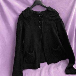 Stickad tröja med knappar längst upp och öppen nertill