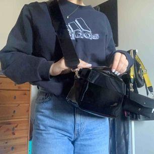 Svart handväska i lack från H&M. Säljs inte längre. Ett fack med mycket utrymme. Avtagbart axelband. Köpare står för frakt 💞
