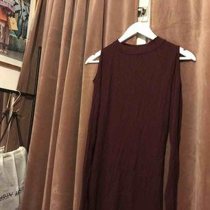 Skitsnygg vinröd/lila klänning i stretchigt material och med öppna axlar