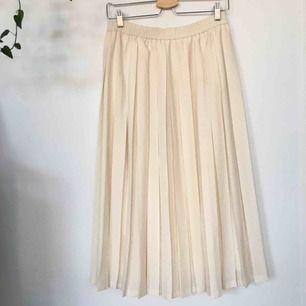 Off-white plisserad kjol! Når till mitten av smalbenet. Resår i midjan och innerkjol.