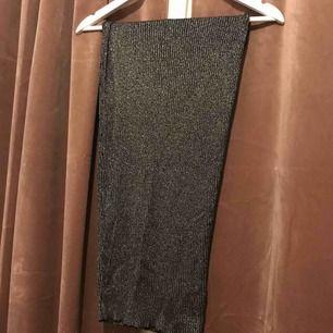 Snygg långkjol i glittrigt och stretchigt material. Resår i midjan.