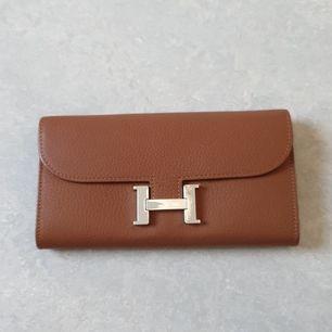 Konjak färgad plånbok från Hermes, i äkta läder, väldigt bra kopia. 12 kortfack, ett fack bakom kortfacken och ett fack med kedja i mitten.
