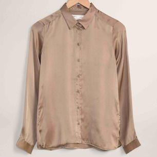 """100% silkesskjorta från InWear. Aldrig använd och är därför i nyskick. Färgen är ljust """"träbrun"""". Nypris är 1000 kr. Frakt 30 kr."""