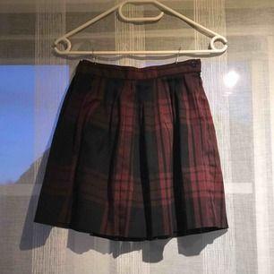 Röd och svart rutig kjol med dragkedja och knapp i sidan. Köps secondhand men jättebra skick, ser ut att inte vara använd. 🖤❤️