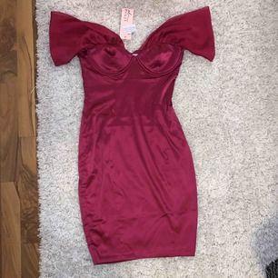 https://www.ohpolly.com/the-last-dance-satin-dress-berry  Visar hur klänningen ser ut på  En oanvänd off-shoulder klänning från Oh Polly i strl 38, den är i siden med ett mjukt glänsande chiffong vid armarna. Ordinariepris ca 520kr.