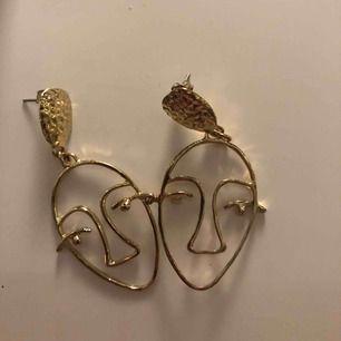 Guldiga örhängen med ansikten från Glitter. Knappt använda. Nypris: 30 kr