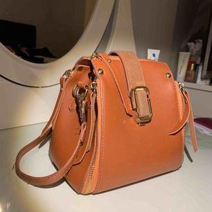 Väldigt unik väska i brun färg med dragkedja, axelband och magnet flärp. Mycket bra skick, vid intresse kan jag skicka fler bilder.