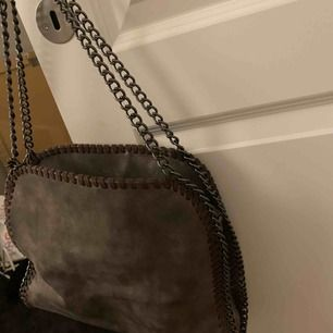 Liknande Stella McCartney väska i grå färg, går att ha på axeln och även som crossover.