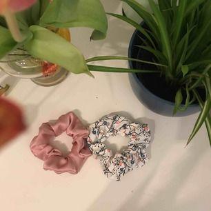 En rosa scrunchie och en vit med rosa och blåa blommor. 25kr för en eller 45kr för båda🦋🌸🤍