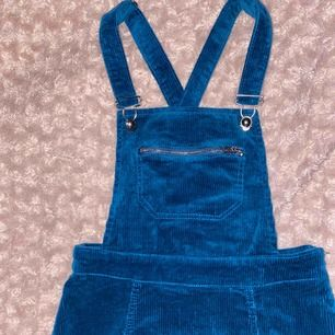 En skitsöt hängselklänning (vet inte riktigt hur jag ska beskriva) i blå(velvet) färg. Har en dragkedja vid ena sidan och går även att justera banden. Är 152cm kort och klänningen går till låren (ca 4-5cm ovanför knäna) Frakt redan inräknat!💙