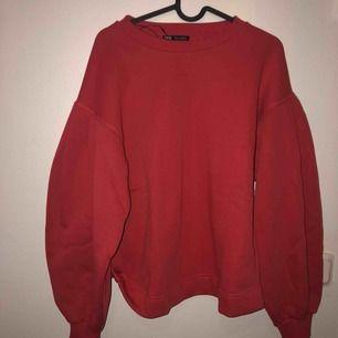 Röd sweatshirt med ballongarm från ZARA. Helt onanvänd. Första bilden med blixt andra utan. Frakt tillkommer på 63kr.