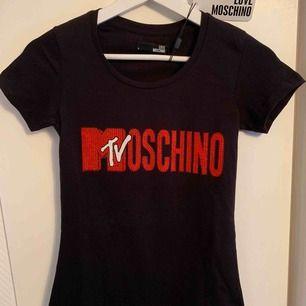Oanvänd märkes t-shirt från MOSCHINO för tjejer Storlek: S  —— OBS: KÖPAREN STÅ FÖR FRAKTEN! - Frakt med spårnummer kostar 63kr