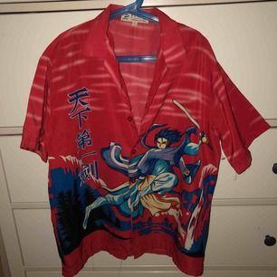 En röd kortärmad skjorta med någon animerad gubbe på, inte använd så mycket. Står ingen storlek men skulle tro S.