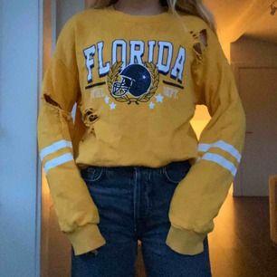 Gul tröja ifrån Gina Tricot i storlek S. Tröjan har ett tryck där det står Florida🧡