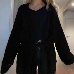 En svart stickad kofta med ett skärp. Helt oanvänd och väldigt snygg.