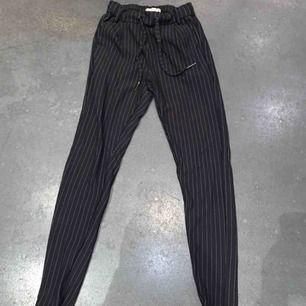 Ett par svarta kostymbyxor med vita smala ränder, knappt använda. Köptes i somras. Passar från xs till m. Köparen står för frakt