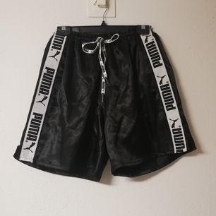 Svarta 90-tals nostalgiska Puma shorts i stl L, går att dra åt i midjan rejält så funkar på mindre. Frakt 42 kr.