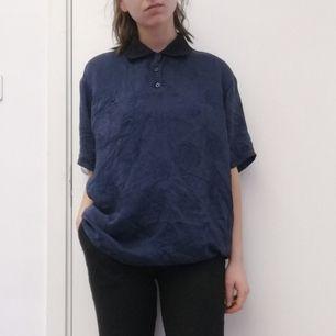 Vintage mörkblå pikétröja med diskret orientaliskt mönster (bild 2 tagen med blixt för att mönstret ska synas). Gjord i 100% siden. Sitter snyggt oversize på mig som har XS. Frakt 42 kr.