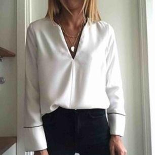 En vit blus med svarta detaljer, använd 1-2 gånger. Köpt i våras. Passar perfekt till en kavaj eller svarta kostymbyxor. Köparen står för frakt