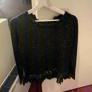 En stickad glittrig tröja med jättefin rygg. Använd någon gång men inte riktigt min stil. Passar en xs-m. I väldigt bra skick. Köparen står för frakt