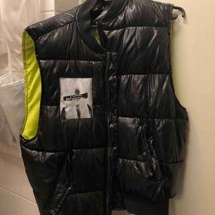 Glansig svart väst från H&M med neongrön insida. Köpte förra året, men använder tyvärr aldrig längre. Stor i storleken och passar även M eller L, bra skick!