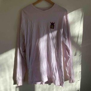 En vit/rosa/lila färgad Stüssy longsleeve, se bild 2 för några knappt synbara fläckar som förmodligen går bort med lite vanish eller