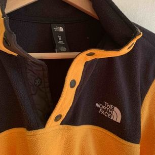 En north face fleece i färgerna gul & svart. Logga fram på bröstet. Knappar upptill! Knappt använd därav nyskick 🌻