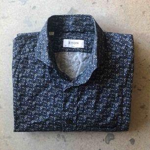Enkel mörkblå bomullsskjorta från Eton. Diskret blommönster som piggar upp garderoben. Använd ett fåtal gånger, i bra skick. Stl 43, XL i slim fit.