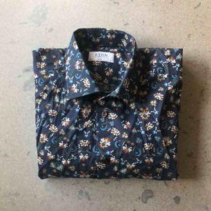 Unik mörkblå bomullsskjorta från Eton. Orangea och ljusblå blomdetaljer gör att den står ut i mängden! Stl 43, XL i slimfit. Använd fåtal gånger, i bra skick.