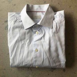 Blårandig klassisk vit bomullsskjorta från Eton. Stl 43/17, XL i passformen slim fit. Använd ett fåtal gånger, i bra skick.