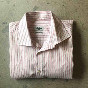 Rosa/röd randig vit skjorta från Stenströms. Använd ett fåtal gånger, i bra skick. Stl 43/17 XL.