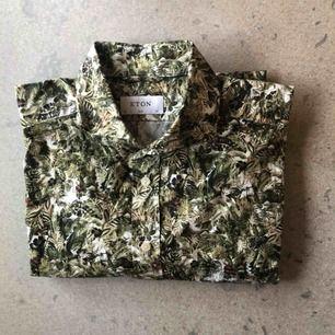 Militärmönstrad bomullsskjorta från Eton. Stl 43/17 XL i passformen slimfit. Använd ett fåtal gånger, i bra skick.