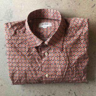 Färgglad, rödaktig bomullsskjorta från Eton. Stl 43/17 XL, i slimfit. Använd ett fåtal gånger, i bra skick.