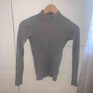Grå, ribbad tröja med en kort polo krage från Gina Tricot! Sitter superfint och framhäver kroppsformen! Frakt tillkommer