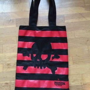 Sparsamt använd väska i svart&rött med en döskalle. Svart baksida. Perfekt att hänga på axeln. Väldigt rymlig. Priset är inkl vanlig frakt 🌸