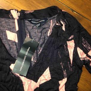 Oanvänd klänning från French Connection  Super fin i marinblå och rosa färg, dragkedja i ryggen  Sitter lite tajtare i midjan med korta armar  Aldrig använd pga för liten Kan frakta (köparen står då för frakten) eller mötas upp i centrala Stockholm 😊