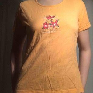Det här är en t-shirt som är orange aprikos T-shirt med ett tryck med röda blommor