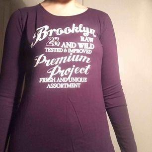 Det här är en tröja från Tribute som är mörklila och har en vit text.